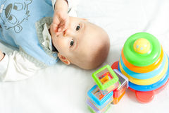 Baby and toys. Little boy lying down on the bed wis toys Royalty Free Stock Photo