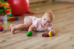Baby with toys on the floor Stock Images