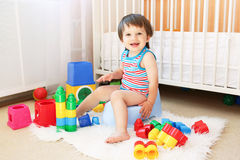 Baby with toys sitting on potty Stock Photography