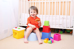 Baby with toys and waffle sitting on potty. Lovely baby boy with toys and waffle sitting on potty stock images