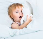 Baby with a toys in white bed Royalty Free Stock Images