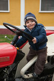 Baby on tractor old. Baby with hat driving a tractor old Stock Photo