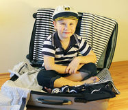 Baby in the travel suitcase. Boy in a sailor dress sitting in a suitcase with clothes in a marine style Royalty Free Stock Photography