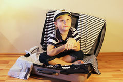 Baby in the travel suitcase. Boy in a sailor dress sitting in a suitcase with clothes in a marine style Stock Photography