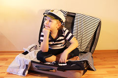 Baby in the travel suitcase. Boy in a sailor dress sitting in a suitcase with clothes in a marine style Stock Image
