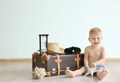 Baby with travel suitcase at home. Holiday concept Royalty Free Stock Photo