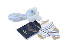 Baby Travels. Shown by a baby rattle and booties with a passport for traveling - path included Royalty Free Stock Photos