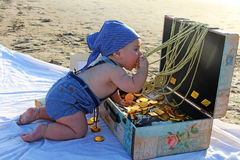 A baby and a treasure chest. On the beach Royalty Free Stock Image