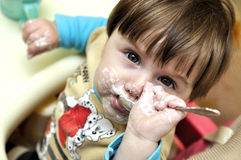 Baby tries to eat yoghurt independently Stock Photography