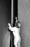 Baby tries to open the door.  Stock Images