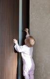 Baby tries to open the door.  Stock Photo