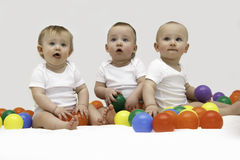 Baby triplets engaged and playing with colorful balls royalty free stock images