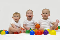 Baby triplets laughing and playing with colorful balls stock images