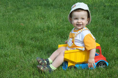 A baby in the truck on the grass. A smiling baby with a pacifier is sitting in the toy truck on the grass Royalty Free Stock Images