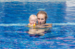 Baby try to swim. Mom teaches the child to swim  in the swimming pool Stock Image