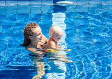 Baby try to swim. Mom teaches the child to swim  in the swimming pool Stock Photography