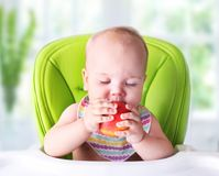 Baby trying first food.Child with apple. stock photography