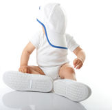 Baby trying on shoes and basebal cap. Adorable baby trying on shoes and basebal cap that are way too big for him Royalty Free Stock Images