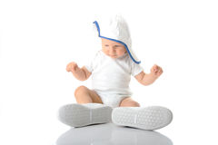 Baby trying on shoes and basebal cap Stock Photography
