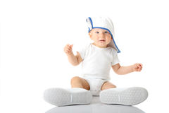 Baby trying on shoes and basebal cap. Adorable baby trying on shoes and basebal cap that are way too big for him Royalty Free Stock Photo