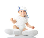 Baby trying on shoes and basebal cap Stock Photo