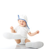 Baby trying on shoes and basebal cap. Adorable baby trying on shoes and basebal cap that are way too big for him Stock Photo