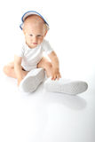 Baby trying on shoes and basebal cap. Adorable baby trying on shoes and basebal cap that are way too big for him Stock Image