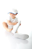 Baby trying on shoes and basebal cap. Adorable baby trying on shoes and basebal cap that are way too big for him Royalty Free Stock Image