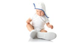 Baby trying on shoes and basebal cap Stock Image