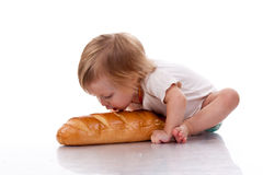 Baby trying to bite a loaf of bread Stock Photo
