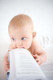 Baby trying to eat a book. Baby with book on white Royalty Free Stock Photos