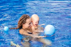 Baby is trying to swim. Baby and mother in the swimming pool Royalty Free Stock Images