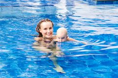 Baby is trying to swim. Baby and mother in the swimming pool Stock Photos