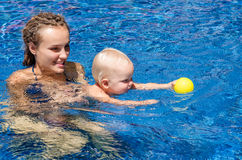 Baby is trying to swim. Baby and mother in the swimming pool Stock Photo