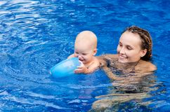 Baby is trying to swim. Baby and mother in the swimming pool Royalty Free Stock Photo