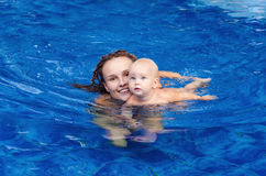 Baby is trying to swim. Baby and mother in the swimming pool Stock Image