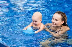 Baby is trying to swim. Baby and mother in the swimming pool Royalty Free Stock Photos
