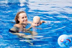 Baby is trying to swim. Baby and mother in the swimming pool Stock Photography