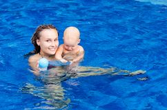 Baby is trying to swim. Baby and mother in the swimming pool Royalty Free Stock Photography