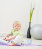 Baby trying to wear big sneakers Royalty Free Stock Photo