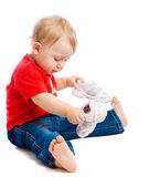 Baby trying on trainers. Baby sitting on floor and trying on trainers Royalty Free Stock Images