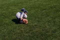 Baby tumbles on green artificial cover outdoors. Boy tumbles on green artificial cover outdoors stock photography