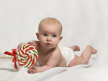 Baby on Tummy with Candy Cane Lollipop Stock Photo