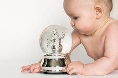Baby on Tummy Looking at Snow Globe Stock Photo