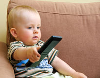 Baby and TV remote Royalty Free Stock Images