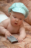 BABY-TV VI. An image of a baby playing with TV control panel Royalty Free Stock Photo