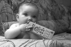 Baby-TV VI. An image of a baby playing with TV control panel Stock Photo
