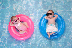 Baby Twin Boy and Girl Floating on Swim Rings. Two month old twin baby sister and brother sleeping on tiny, inflatable, pink and blue swim rings. They are stock photos