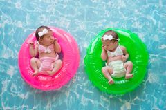 Baby Twin Girls Floating on Swim Rings stock photography