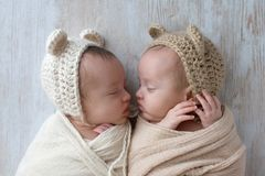 Baby Twin Girls Wearing Bear Bonnets. Profile headshot of two, fraternal, twin, baby girls sleeping. They are wearing crocheted bear hats and are swaddled in stock images